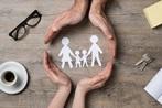 זוג כפות ידיים שמקיפות תמונת נייר של משפחה