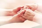 זוג ידיים צעירות אוחזות בזוג ידיים של קשישה
