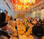 קשישים ישובים ליד שולחן סעודה