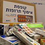 ערימת תרופות ושלט עם כיתוב 'קופסת איסוף תרופות'