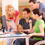 אישה נכה ישובה על כיסא גלגלים מול מחשב ולצידה חברים