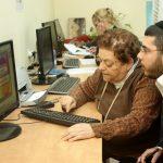 גבר מדריך קשישה לשימוש נכון במחשב
