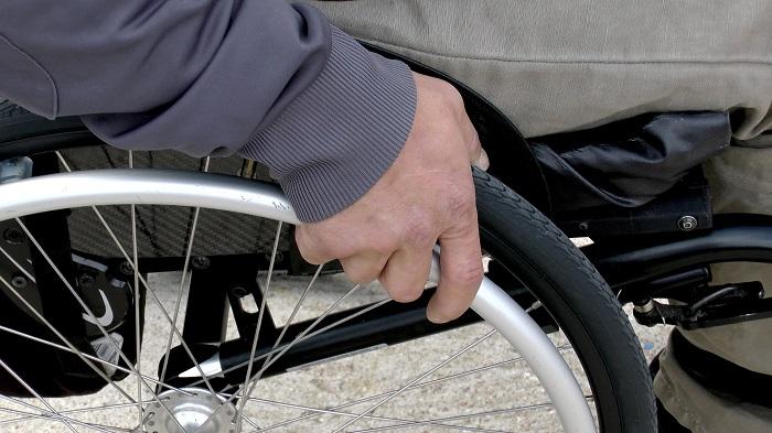 צילום תקריב: אדם יושב על כיסא גלגלים ואוחז בגלגל הימני