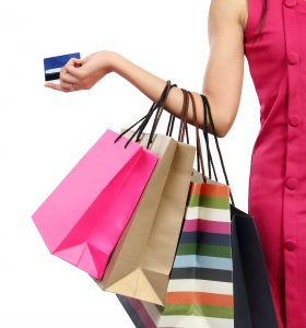 אישה בשמלה ורודה עם כרטיס אשראי ו4 שקיות נייר