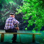 אישר זקן יושב מול מקווה מים ומסביבו עצים