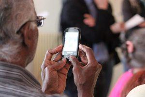 גבר קשיש אוחז בטלפון נייד