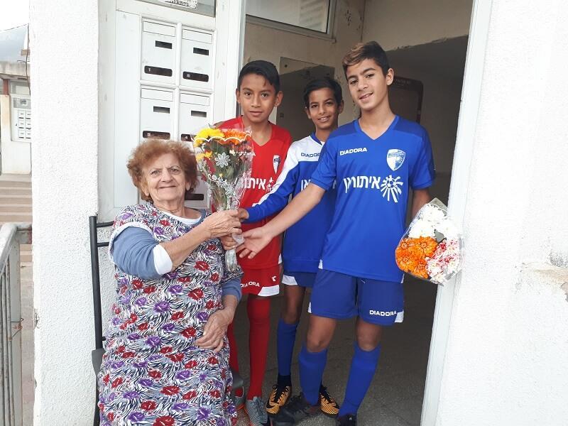 ילדי קבוצת הכדורגל איתוראן של קרית שמונה מבקרים קשישים. צילום: צוות מטב.