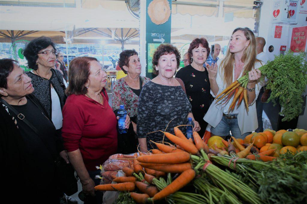 מחזירים אהבה 2018- מיכל אנסקי מארחת קשישות בשוק האוכל בנמל תל אביב. צילום: אלוני מור.